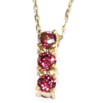 Three Garnet gemstones (1ct.) in a yellow gold pendant setting with 18″ gold chain. $220
